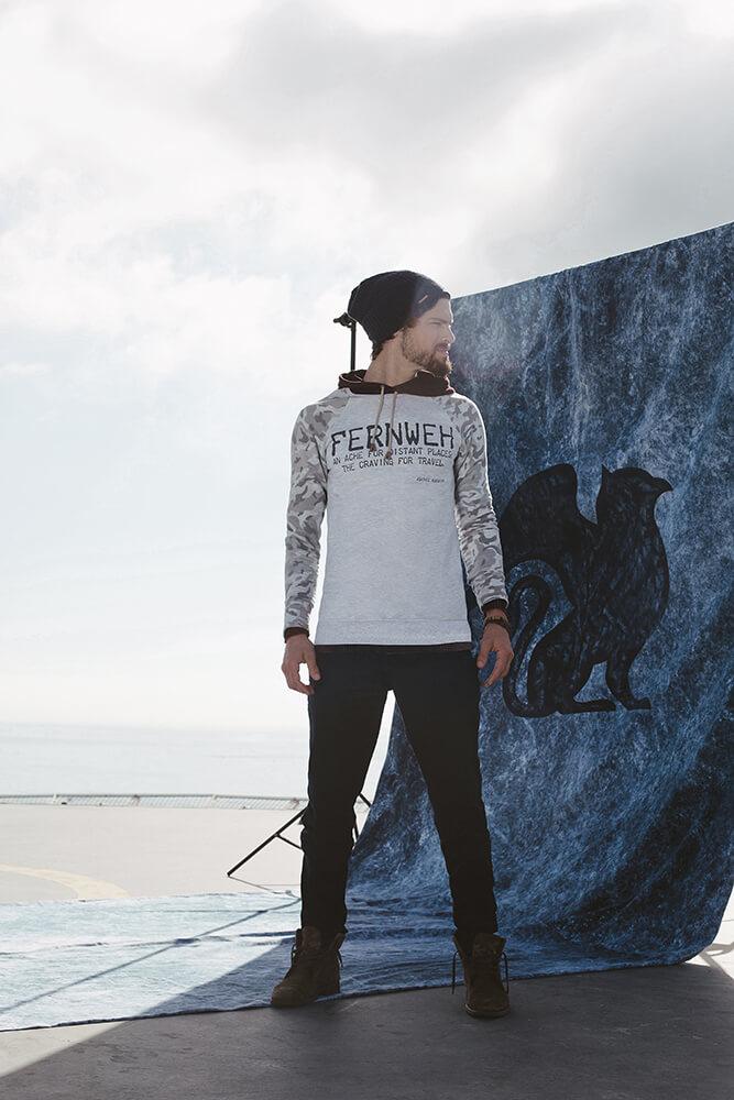 Modelo usando casaco e calça da Agathos pose em frente a um fundo infinito com o logo da Agathos estampado no telhado de um prédio com vista para o mar