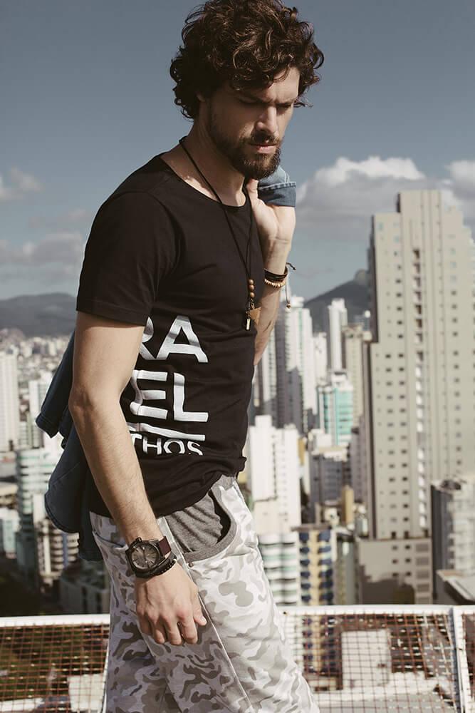 Modelo vestindo camiseta e bermuda da Agathos caminha no telhado de um prédio com vista para outros prédios da cidade